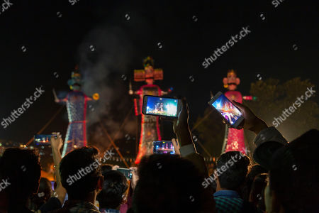 People take cellphone photos of effigies of mythological demon king Ravana, center, his brother and his son, before they are burnt marking the end of Dussehra festival in Dharmsala, India, . Dussehra commemorates the triumph of Lord Rama over the demon king Ravana, marking the victory of good over evil