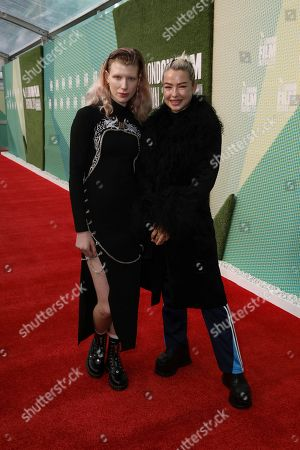 Influencer Charlie Barker, left, and Model Jessica Anne Woodley, pose for photographers on arrival at the Premiere of the film 'Portrait of a Lady On Fire' which is screened as part of the London Film Festival in central London on