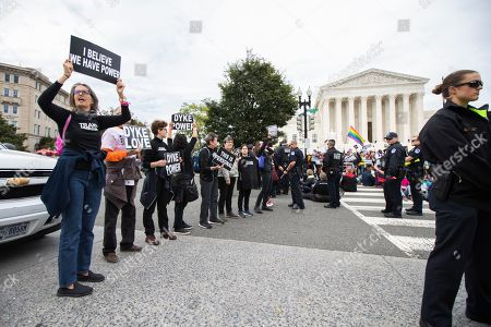 Supporters of LGBT rights protest on the street in front of the U.S. Supreme Court, wave their placards as they were arrested, in Washington. The Supreme Court is set to hear arguments in its first cases on LGBT rights since the retirement of Justice Anthony Kennedy. Kennedy was a voice for gay rights while his successor, Brett Kavanaugh, is regarded as more conservative