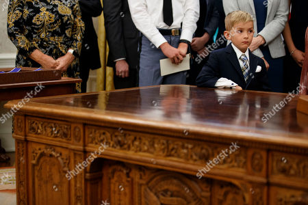 A 6 year old boy, leans on the Resolute Desk as President Donald Trump speaks during a ceremony to present the Presidential Medal of Freedom to former Attorney General Edwin Meese, in the Oval Office of the White House, in Washington