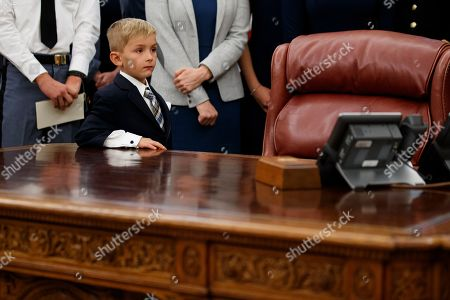 Stock Picture of A 6 year old boy, leans on the Resolute Desk as President Donald Trump speaks during a ceremony to present the Presidential Medal of Freedom to former Attorney General Edwin Meese, in the Oval Office of the White House, in Washington