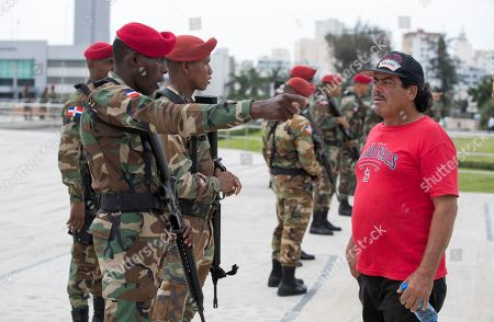Members of the Dominican Army guard as supporters of former President and Presidential pre-candidate Leonel Fernandez demonstrate against the results of primary elections held on 06 October, in front of the headquarters of the Central Electoral Board in Santo Domingo, Dominican Republic, 08 October 2019. Fernandez does not recognize the results of the PLD primaries, which was won by a narrow margin by former minister Gonzalo Castillo, elected candidate of the official formation for the May 2020 elections.
