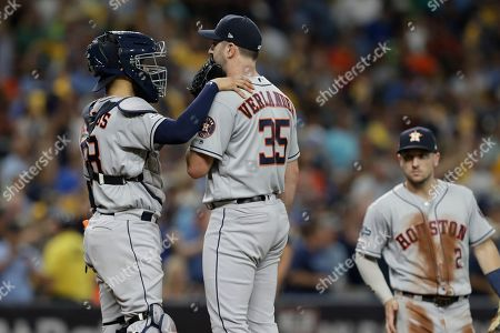 Houston Astros starting pitcher Justin Verlander (35) talks to catcher Robinson Chirinos as third baseman Alex Bregman (2) looks on against the Tampa Bay Rays during Game 4 of a baseball American League Division Series, in St. Petersburg, Fla