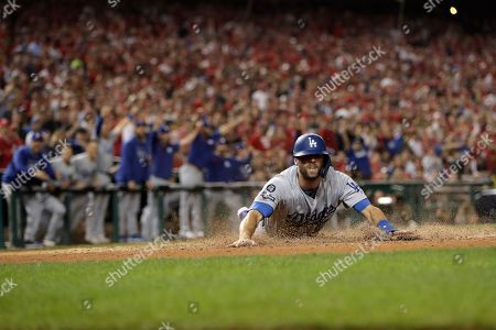 Los Angeles Dodgers' Chris Taylor slides into home while scoring on a double by Enrique Hernandez during the sixth inning of Game 3 of a baseball National League Division Series against the Washington Nationals, in Washington