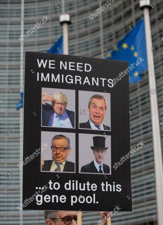 A man holds a poster with the photos of, clockwise from top left, British Prime Minister Boris Johnson, Brexit Party leader Nigel Farage, Leader of the House of Commons Jacob Rees-Mogg, and British lawmaker Michael Gove during an anti-Brexit protest outside European Commission headquarters in Brussels, . A small group of anti-Brexit campaigners staged the protest asking for a rejection of British Prime minister Boris Johnson's proposals for his country's planned exit from the bloc