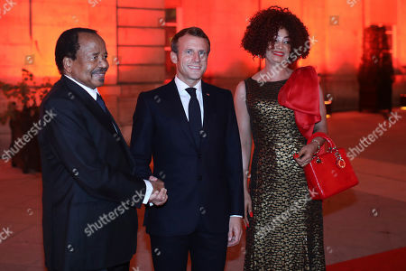 France's President Emmanuel Macron shakes hands with Cameroon President Paul Biya, left, at the Lyon's city hall, central France, during the meeting of international lawmakers, health leaders and people affected by HIV, Tuberculosis and malaria. Lyon is hosting the two day Global Fund event aimed at raising money to help in the global fight against the epidemics