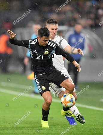 Germany's Niklas Suele, right, challenges for the ball with Argentina's Paulo Dybala during the international friendly soccer match between Germany and Argentina at the Signal Iduna Park stadium in Dortmund, Germany