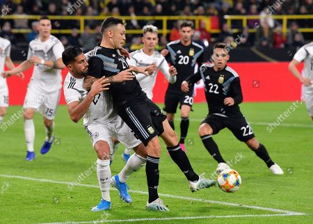 Argentina's Lucas Ocampos passes the ball held by Germany's Emre Can, left, during the international friendly soccer match between Germany and Argentina at the Signal Iduna Park stadium in Dortmund, Germany