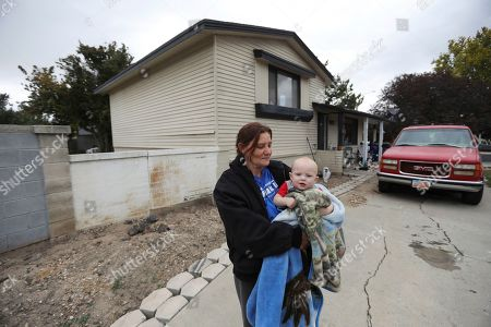 Stock Image of Alanna Mabey holds her grandson in front of her home, in West Valley City, Utah. Paul Petersen sold the house this spring as complaints mounted from neighbors in the working-class area in suburban Salt Lake City, said new owner Mabey. Authorities say Petersen used homes like this one to lodge pregnant women from the Marshall Islands who were offered money to come to the U.S. to give up their children for adoption. Petersen, the assessor of Arizona's most populous county, was charged in Utah, Arizona and Arkansas with counts including human smuggling, sale of a child, fraud, forgery and conspiracy to commit money laundering