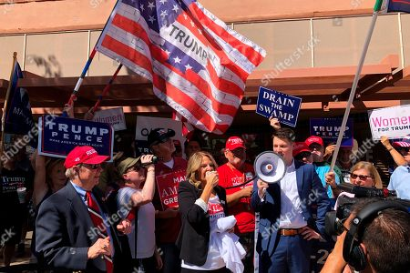 Arizona Republican Party Chairman Kelli Ward speaks to a crowd outside a field office for Rep. Tom O'Halleran, D-Ariz., as GOP spokesman Zachery Henry holds the bullhorn, in Casa Grande, Ariz. While President Donald Trump plays defense on impeachment in Washington, Republicans are taking the fight to Democrats in the states. The national party has drawn up a list of more than 60 target races for the House, Senate and governor where Democrats are running in districts or states carried by Trump, aiming to make impeachment a central theme in those races