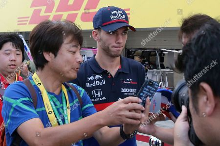 Toro Rosso driver Pierre Gasly of France is taken a photo by a fan, left, upon arrival for a fan meeting at the Suzuka Circuit in Suzuka, central Japan, ahead of the Japanese Formula One Grand Prix