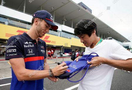 French Formula One driver Pierre Gasly (L) of Scuderia Toro Rosso signs autographs to a fan ahead of the Japanese Formula One Grand Prix in Suzuka, Japan, 10 October 2019. The Japanese Formula One Grand Prix will take place on 13 October 2019.