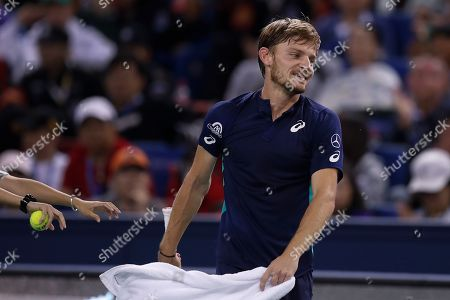 Stock Photo of David Goffin of Belgium reacts as he plays against Roger Federer of Switzerland during their men's singles match at the Shanghai Masters tennis tournament at Qizhong Forest Sports City Tennis Center in Shanghai, China
