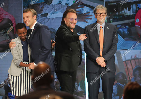 """From left to right, goodwill ambassador of the ONG """"Grandir Ensemble"""" Amanda Dushime, France's President Emmanuel Macron, U2 singer Bono and Philanthropist and Co-Chairman of the Bill & Melinda Gates Foundation Bill Gates congratulate each other on stage during the Global Fund to Fight AIDS event at the Lyon's congress hall, central France, . French President Emmanuel Macron said the conference of the Global Fund to fight against AIDS, tuberculosis and malaria raised at least $13.92 billion for the next three years"""