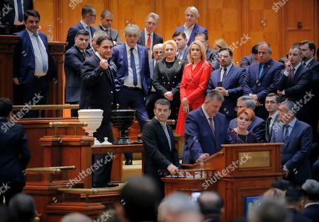 An opposition lawmaker clenches his fist after voting as Romanian Prime Minister Viorica Dancila watches along with government members of a no confidence vote in Bucharest, Romania, . Romania's Social Democrat government has lost a vote of no-confidence in Parliament