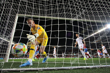 Jordan Pickford of England gathers the ball from goal netting after conceding 1st goal while Harry Kane of England looks dejected behind
