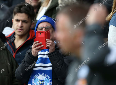 Stock Photo of A Peterborough fan takes a picture on his phone of Peterborough manager Darren Ferguson