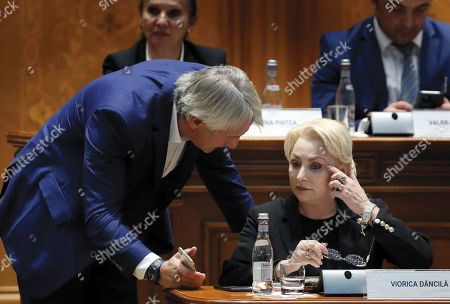 Romanian Finance Minister Eugen Teodorovici (L) shows the screen of his smartfone to Romania's Prime Minister Viorica Dancila (R) shortly after she was addressing  the lawmakers of both parliament chambers, as she faces a no-confidence vote at Parliament Palace in Bucharest, Romania, 10 October 2019. The opposition parties pushed a no-confidence vote against the ruling coalition after the junior partner of the  ruling coalition, ALDE party, pulled out of the government in August, leaving the senior PSD party without a majority. For the no-confidence vote to pass, it needs the support of 233  lawmakers from the total number of 465.