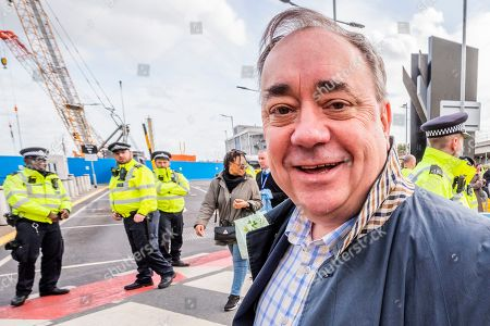 Alex Salmond of the SNP arrives, he has no comment about the protest behind him, just saying 'I am here for a flight' while protestors attempt to shut London City Airport down on the fourth day of the Extinction Rebellion October action