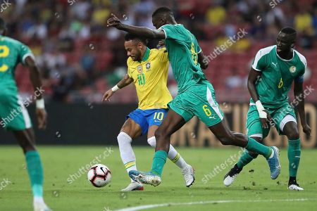 Brazil's Neymar, center, and Senegal's Salif Sane in action during the Brazil Global Tour 2019 international friendly soccer match between Brazil and Senegal in Singapore