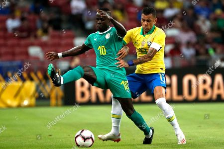 Stock Image of Sadio Mane  (L) of Senegal in action against Dani Alves (R) of Brazil during an international friendly match at the National Stadium in Singapore, 10 October 2019.