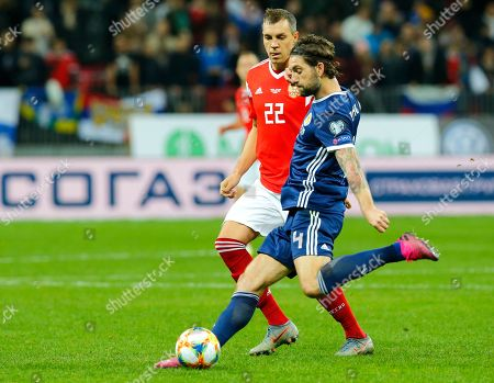 Scotland's Charlie Mulgrew, right, kicks the ball ahead of Russia's Artem Dzyuba during the Euro 2020 group I qualifying soccer match between Russia and Scotland at the Luzhniki Stadium in Moscow, Russia