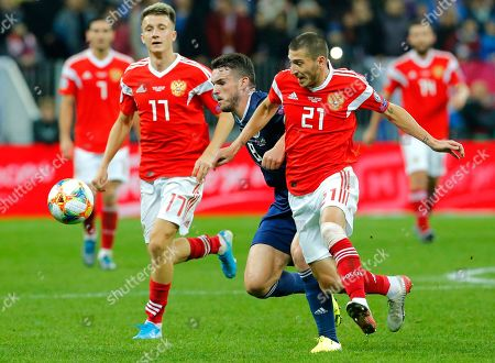 Russia's Aleksandr Golovin, left, Russia's Aleksei Ionov, right, and Scotland's John McGinn challenge for the ball during the Euro 2020 group I qualifying soccer match between Russia and Scotland at the Luzhniki Stadium in Moscow, Russia