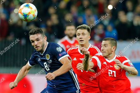 Russia's Aleksandr Golovin, centre, Russia's Aleksei Ionov, right, and Scotland's John McGinn challenge for the ball during the Euro 2020 group I qualifying soccer match between Russia and Scotland at the Luzhniki Stadium in Moscow, Russia