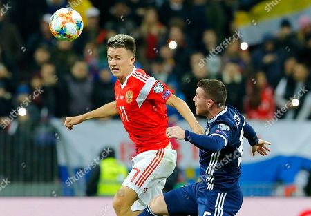 Russia's Aleksandr Golovin, left, and Scotland's John Fleck challenge for the ball during the Euro 2020 group I qualifying soccer match between Russia and Scotland at the Luzhniki Stadium in Moscow, Russia