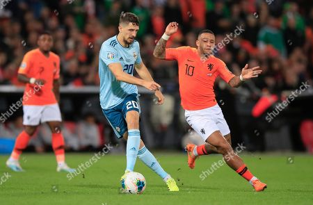 Northern Ireland's Craig Cathcart, left, challenges for the ball with Netherlands' Memphis Depay during the Euro 2020 group C qualifying soccer match between The Netherlands and Northern Ireland at De Kuip stadium in Rotterdam, Netherlands