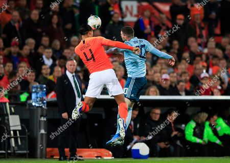 Netherlands' Virgil van Dijk jumps for a header with Northern Ireland'sKyle Lafferty during the Euro 2020 group C qualifying soccer match between The Netherlands and Northern Ireland at De Kuip stadium in Rotterdam, Netherlands