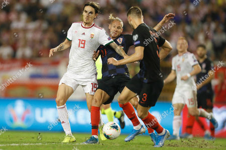 Domagoj Vida, Borna Barisic, David Holman. Croatia's Domagoj Vida, center, and Borna Barisic, right, fights for the ball with Hungary's David Holman, left, during the Euro 2020 group E qualifying soccer match between Croatia and Hungary at Poljud stadium in Split, Croatia