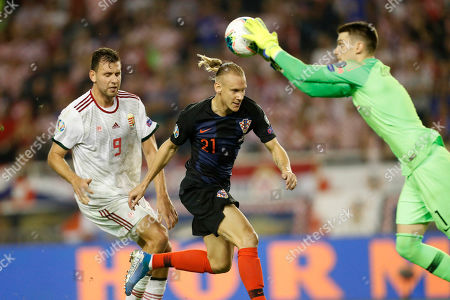 Dominik Livakovic, Domagoj Vida, Adam Szalai. Croatia's goalkeeper Dominik Livakovic controls ball by his teammate Domagoj Vida, center, and Hungaria's Adam Szalai during the Euro 2020 group E qualifying soccer match between Croatia and Hungary at Poljud stadium in Split, Croatia