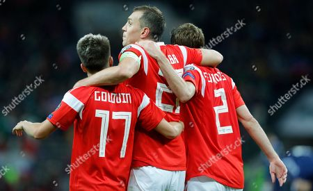 Russia's Artem Dzyuba, centre, Aleksandr Golovin, left, and Mario Fernandes celebrate their side's fourth goal scored by Aleksandr Golovin, right, during the Euro 2020 group I qualifying soccer match between Russia and Scotland at the Luzhniki Stadium in Moscow, Russia