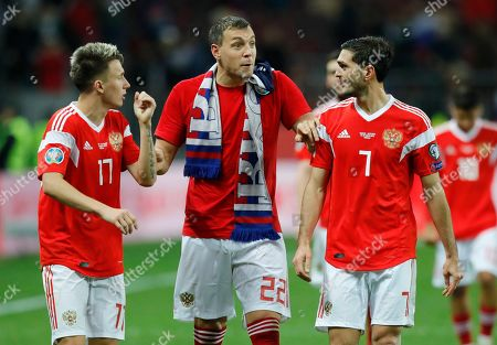 Russia's Artem Dzyuba, centre, Aleksandr Golovin, left, and Magomed Ozdoev celebrate their 4-0 victory in the Euro 2020 group I qualifying soccer match between Russia and Scotland at the Luzhniki Stadium in Moscow, Russia