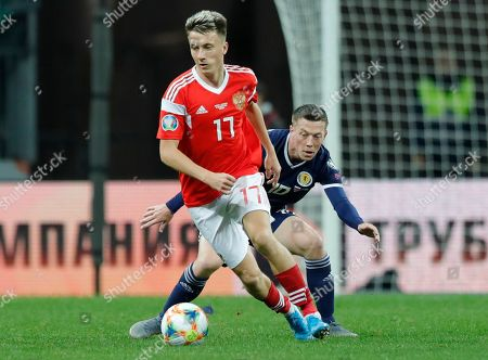 Russia's Aleksandr Golovin, front, fights for the ball with Scotland's Callum McGregor during the Euro 2020 group I qualifying soccer match between Russia and Scotland at the Luzhniki Stadium in Moscow, Russia