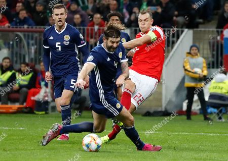 Scotland's Charlie Mulgrew, centre, fights for the ball with Russia's Artem Dzyuba, right, during the Euro 2020 group I qualifying soccer match between Russia and Scotland at the Luzhniki Stadium in Moscow, Russia
