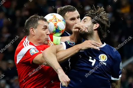 Russia's Artem Dzyuba, left, fights for the ball with Scotland's Michael Devlin, centre, and Charlie Mulgrew during the Euro 2020 group I qualifying soccer match between Russia and Scotland at the Luzhniki Stadium in Moscow, Russia