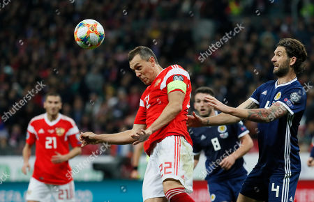Artem Dzyuba (C) of Russia ia action against Charlie Mulgrew (R) of Scotland during the UEFA 2020 Qualifying round - Group I soccer match of Russian and Scotch national teams at Luzhniki stadium in Moscow, Russia, 10 October 2019.