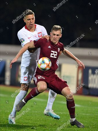 Latvia Israel Euro 2020 Soccer Vladislavs Gutkovskis Jan Bednarek. Latvia's Vladislavs Gutkovskis, right, is challenged by Poland's Jan Bednarek, during their Euro 2020 group G qualifying soccer match in Riga, Latvia