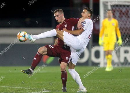 Poland's Jan Bednarek (R) fights for the ball with Latvia's Vladislavs Gutkovskis during the UEFA EURO 2020 Group G qualifying soccer match between Latvia and Poland in Riga, Latvia, 10 October 2019.