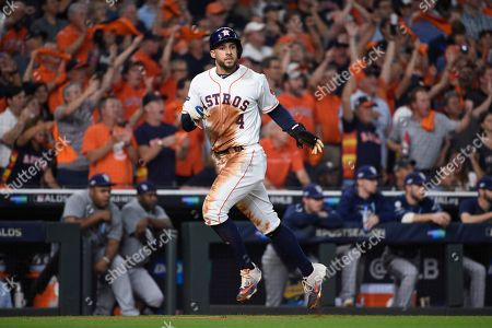 Houston Astros center fielder George Springer (4) scores against the Tampa Bay Rays on teammates Jose Altuve's hit during the first inning of Game 5 of a baseball American League Division Series in Houston