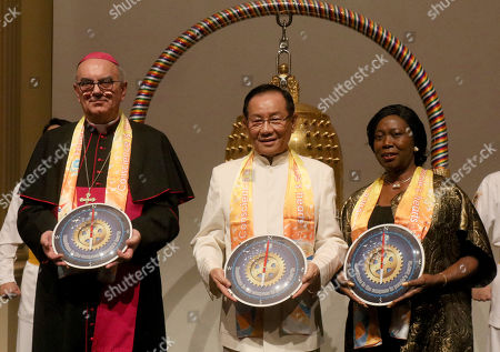 Dr. Camillo Ballin, Apostolic Vicar of Northern Arabia, left, and Youngor Telewoda, Ambassador of Liberia to Austria, right, are each presented with a compass clock of conscience by Dr. Hong, Tao-Tze, president of the Federation of World Peace and Love, after their ringing the Bell of World Peace and Love during a gala dinner in celebration of the United Nations' designation of April 5 as the International Day of Conscience