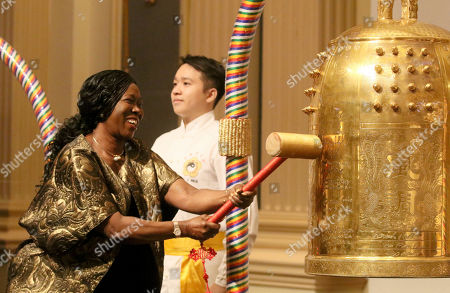 Stock Image of Youngor Telewoda, Ambassador of Liberia to Austria, rings the Bell of World Peace and Love during a gala dinner in Vienna, Austria on . The event was co-organized by the Federation of World Peace and Love, the Permanent Mission of Bahrain to the UN (Vienna), and the Flame of Peace to celebrate the United Nations' designation of April 5 as the International Day of Conscience