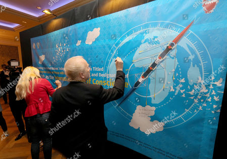 Attendees sign their names on a poster during a gala dinner co-organized by the Federation of World Peace and Love, the Permanent Mission of Bahrain to the UN (Vienna), and the Flame of Peace, in celebration of the United Nations' designation of April 5 as the International Day of Conscience in Vienna, Austria on . The poster conveys the message that all people of the world are in the same boat and should work together for global peace and sustainability
