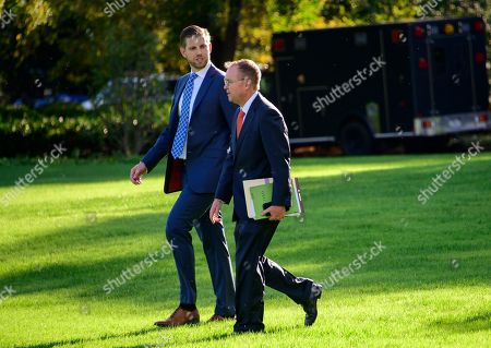 Eric Trump, left, and Acting White House Chief of Staff Mick Mulvaney, right, walk across the South Lawn to accompany United States President Donald J. Trump as he prepares to depart the White House to deliver remarks at a Keep America Great Rally in Minneapolis, Minnesota.