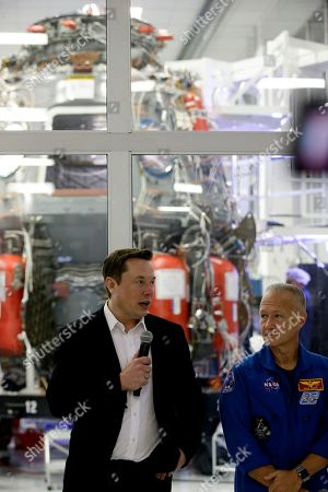 SpaceX chief engineer Elon Musk, left, talks with NASA astronaut Doug Hurley, right, in front of the Crew Dragon spacecraft at SpaceX headquarters about the progress the company is making to fly astronauts to and from the International Space Station, from American soil, as part of the agency's commercial crew program, in Hawthorne, Calif