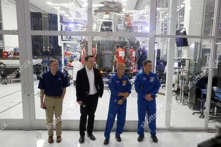 NASA Administrator Jim Bridenstine, left, waits for a question from the media, with SpaceX founder Elon Musk, second from left, and NASA astronauts crew Doug Hurley and Bob Behnken, right, in front of the Crew Dragon spacecraft, about the progress to fly astronauts to and from the International Space Station, from American soil, as part of the agency's commercial crew program at SpaceX headquarters, in Hawthorne, Calif