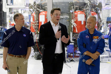 SpaceX founder Elon Musk, center, talks with NASA Administrator Jim Bridenstine, left, and NASA astronauts crew Doug Hurley, right, in front of the Crew Dragon spacecraft, about the progress to fly astronauts to and from the International Space Station, from American soil, as part of the agency's commercial crew program at SpaceX headquarters, in Hawthorne, Calif