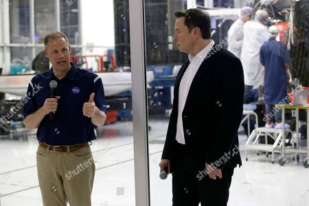 NASA Administrator Jim Bridenstine, left, talks with SpaceX chief engineer Elon Musk, right, in front of the Crew Dragon spacecraft, about the progress to fly astronauts to and from the International Space Station, from American soil, as part of the agency's commercial crew program at SpaceX headquarters, in Hawthorne, Calif